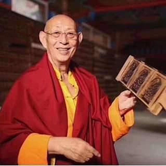 HH Thubten Palzang Rinpoche holding a wooden printing block
