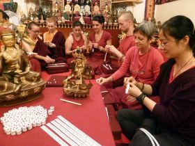 Students making mantra rolls to use in consecrating statues, at the Pathgate Dharma Centre, England