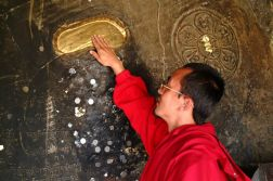 A Tibetan monk seeks blessing from the footprint left by Guru Rinpoche on the wall of the cave where he actually practised with consort Mandarava