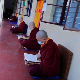 Călugărițe recitând rugăciuni în afara camerelor lor menținând o distanță sigură