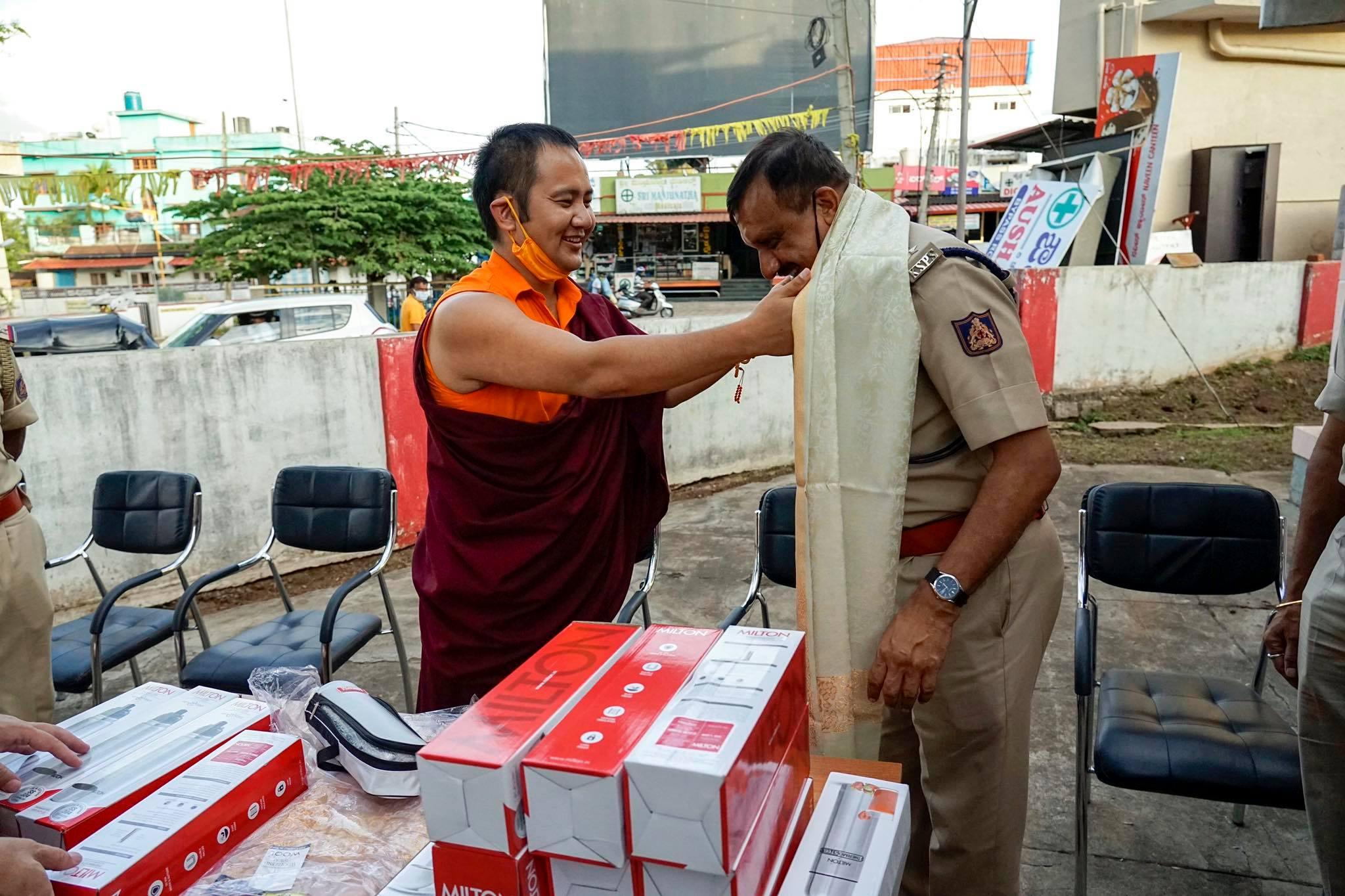 Tulku Tsering Choedhar, Administrator al Fundației de Caritate Penor Rinpoche oferă șalul unui ofițer de poliție