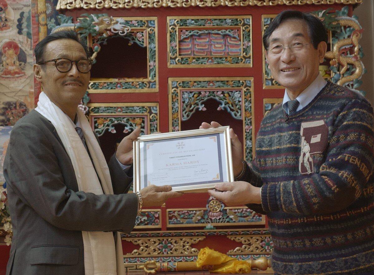 Karma Hardy din stânga a primit certificatul de recunoaștere pentru serviciile sale îndelungate de la Phuntsog Wangyal, Șeful Fundației Tibet, Noiembrie 2020