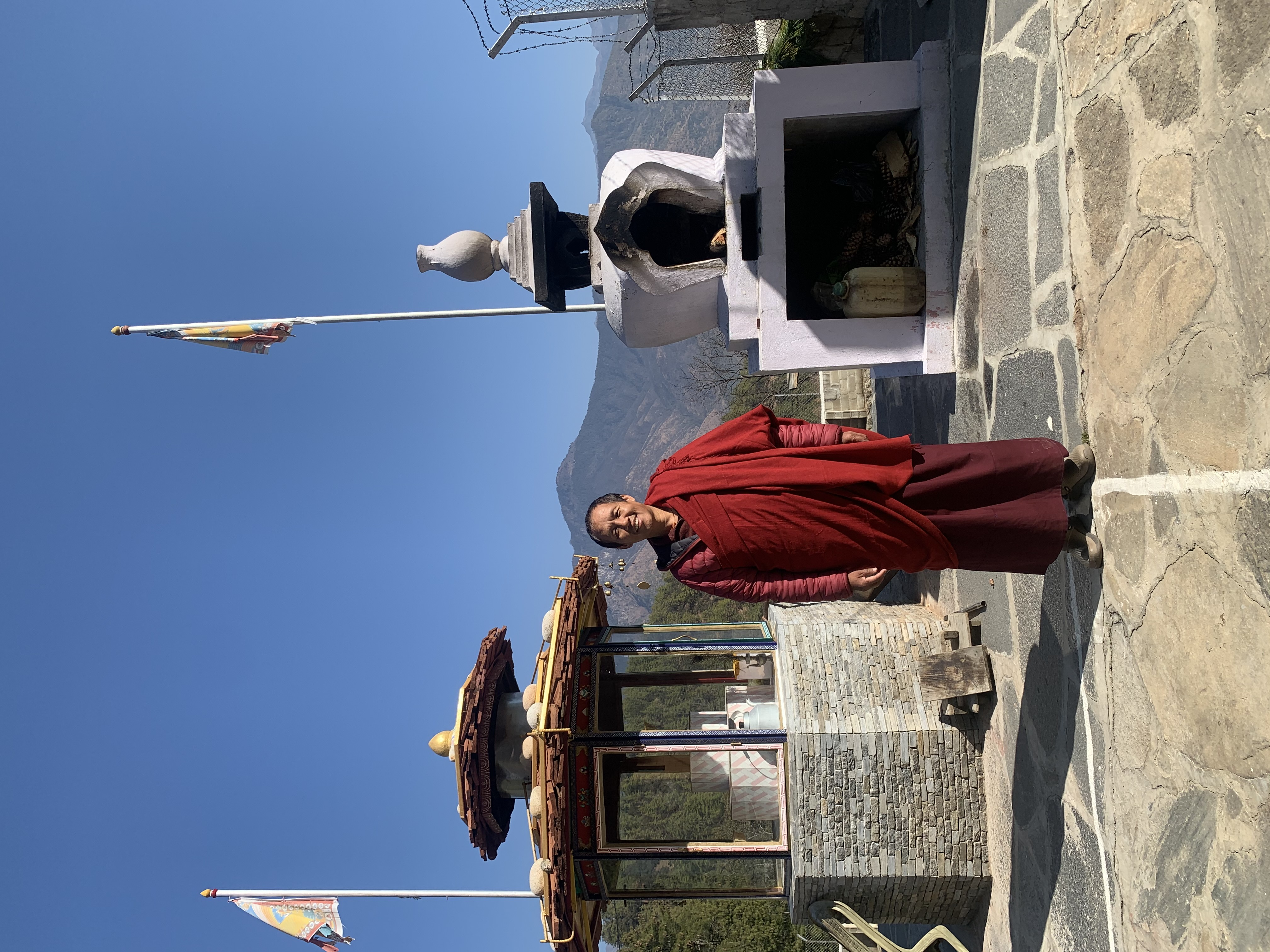 Khenpo Sangay Wangdi Rinpoche standing in between the lamp offering pagoda (left) and the sang offering stupa (right)