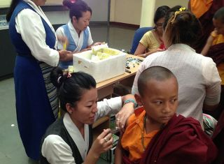 Young monk receiving vaccination